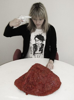 Woman with revolver aimed at her head in front of a giant plate of red goo.