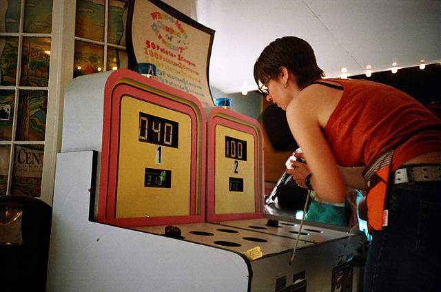 Woman playing whack-a-mole arcade cabinet game.