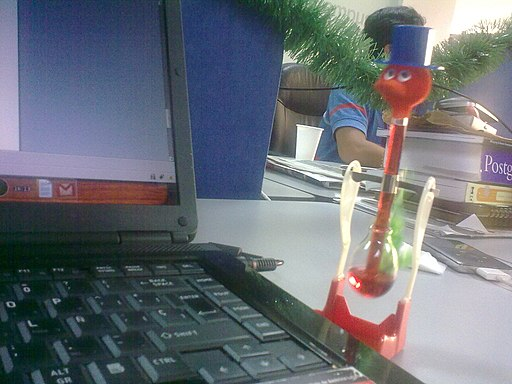 Drinking bird in front of laptop