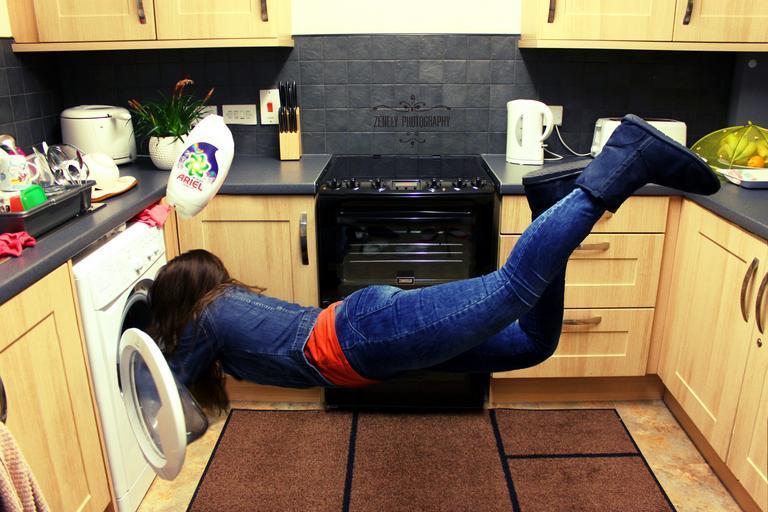 Woman falling down while loading a washing machine