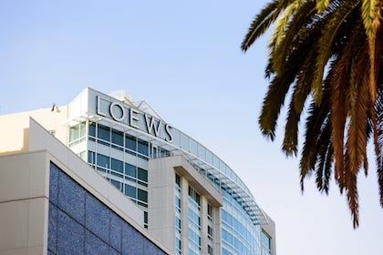 An image of a Loews hotel backdrop with a palm tree peeking in to the corner.