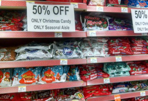 "A picture of christmas candy with ""50% off"" signs at a Walgreens."