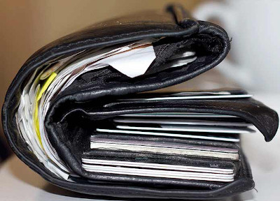 A wallet that is comically stuffed full of cards and papers.