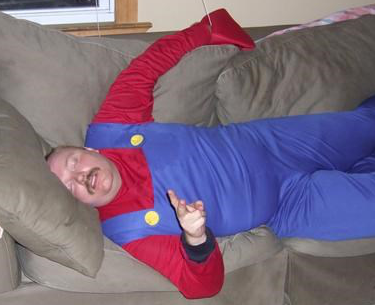 A man passed out on a tan couch wearing a Mario costume.