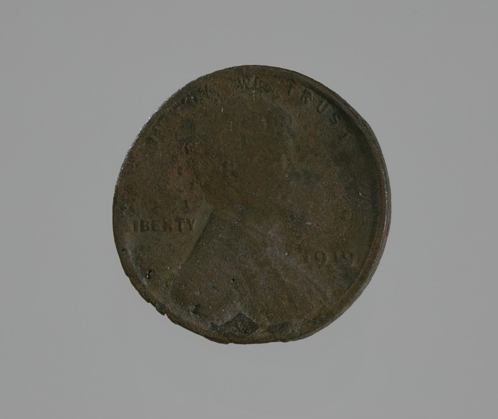 A charred, bent, beat out of shape penny.