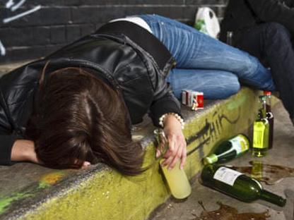 Picture of a person in a black leather jacket laying on the curb, clutching a bottle of alcohol. A wine bottle and other bottles litter the ground.
