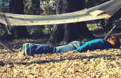 A picture of a boy laying on the ground face down in a pile of leaves, under a hammock.