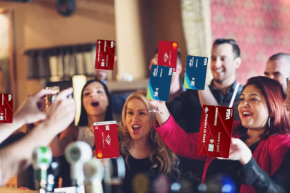 A group of people at a party holding up drinks for a toast, except all of the drinks have been replaced with various Bank of America credit cards