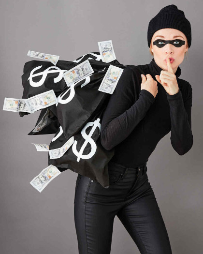 A picture of a woman dressed in a black turtle-neck with black jeans, a black beanie, and a black eye covering carrying black bags with white $ signs and money falling out of the bags.