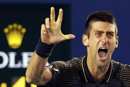 A male tennis player holding up a thumb and two index fingers while screaming