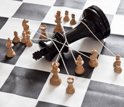 A picture of a king chess piece laying down on a chess board, with lots of opposing chess pieces tying it down with string.