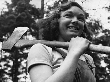 A black and white photo of a woman in overalls with an axe slung over her shoulder, smiling.