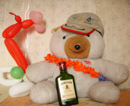 A stuffed bear with a balloon animal behind it. In the bear's lap is a bottle of Jameson Whiskey.