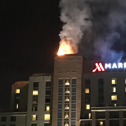A picture showing a fire bellowing out of the top of a tower on a Marriott hotel