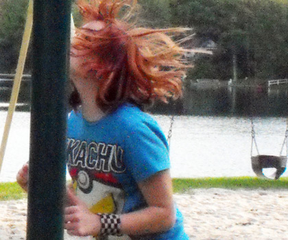 A picture of a woman with red hair and a blue shirt walking into a pole at a playground.