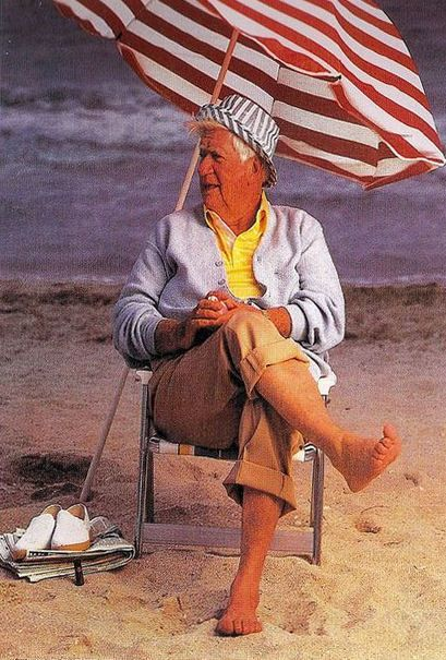 A picture of a barefoot Tip O'Neill on the beach in khaki pants rolled up above the thighs, a sweater with a yellow polo underneath, sunbathing under an american flag styled umbrella.