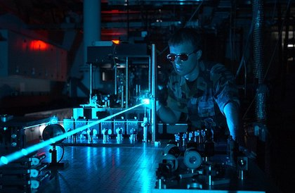 An image of a physicist operating a blue laser with safety goggles in a lab