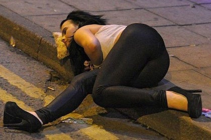 A picture of a woman laying on a curb using a slice of pizza as a pillow.