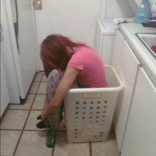 An image of a woman asleep sitting up in a laundry basket.
