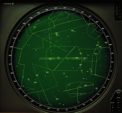 An old, green, monochrome air traffic control radar screen centered on an airport